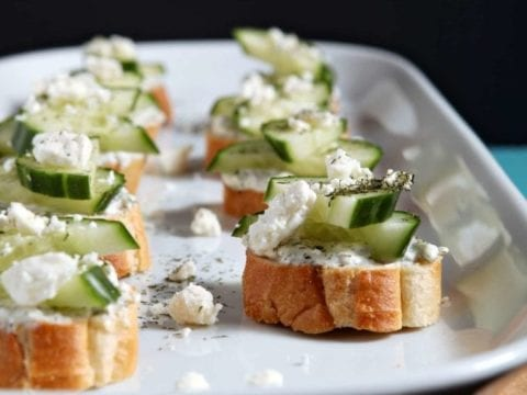 Cucumber Bruschetta, served on a white platter, sits on a wooden background
