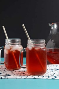 Two iced glasses of Strawberry Sweet Tea sit on a turquoise table with a pitcher