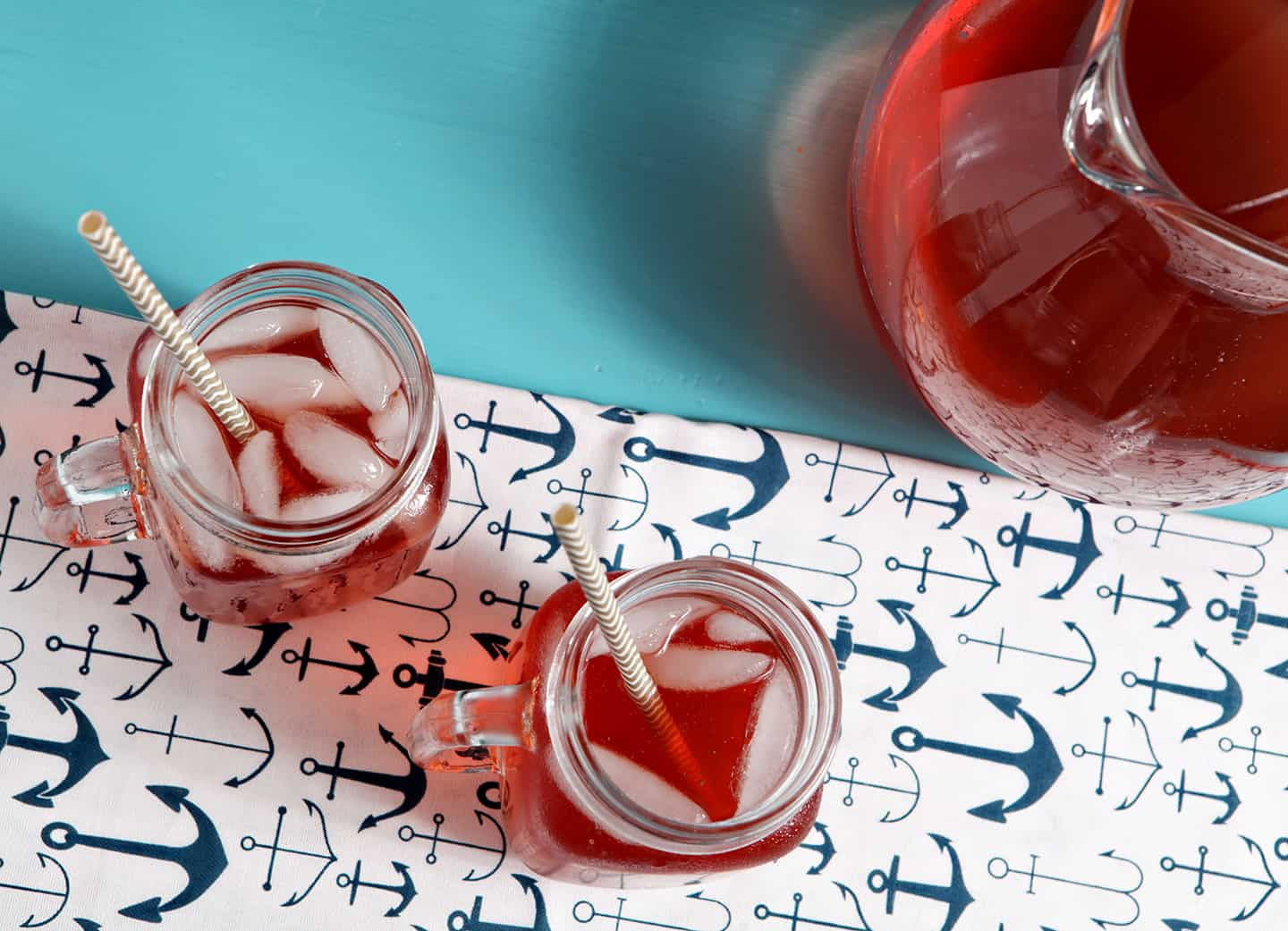 Overhead image of two iced glasses of Strawberry Sweet Tea sitting on a turquoise table with a pitcher