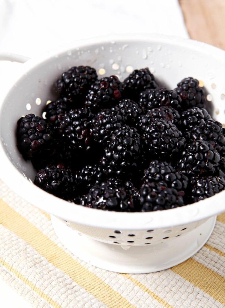 A white colander full of fresh blackberries