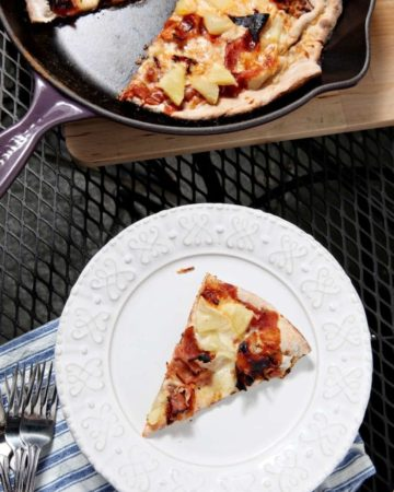 A slice of Grilled Hawaiian Pizza on white plate next to skillet of pizza