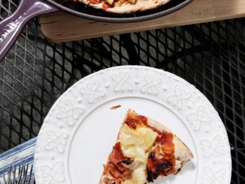 A slice of Grilled Hawaiian Pizza sits on a white platter on an outdoor table with the rest of the pizza, shown in a cast iron skillet.