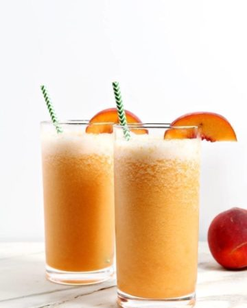 Two Bourbon Peach Slushes, garnished with peach slices and green chevron straws, sit on a marble tile.