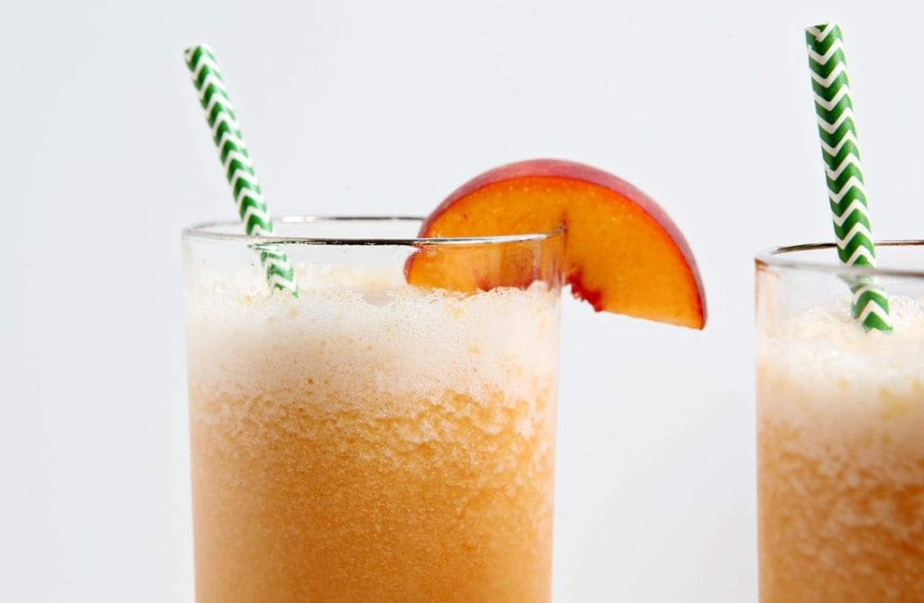 Close up of a highball glass holding a peach bourbon slush, garnished with a peach slice and a green striped straw