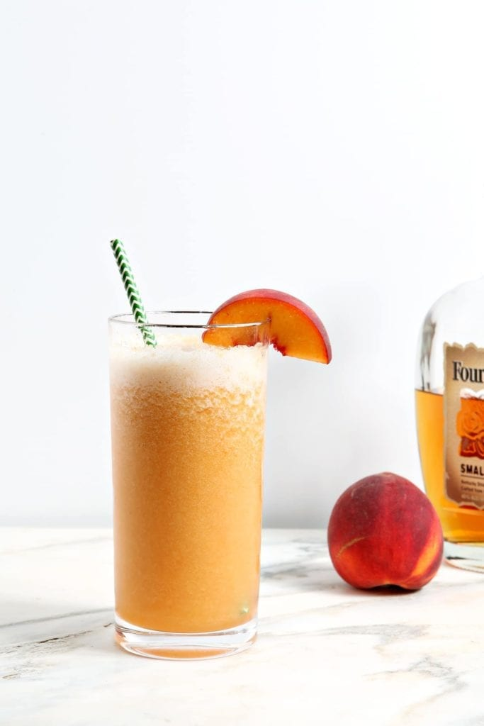 A highball glass holds an orange peach cocktail in it, garnished with a peach, while sitting on a marble background
