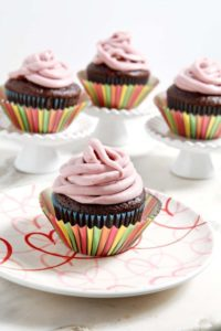 Four Chocolate-Covered Raspberry Cupcakes are displayed before eating, drizzled with Raspberry Cream Cheese Frosting.