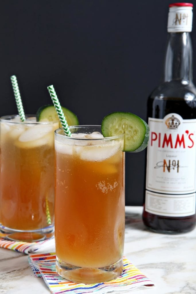 Two Pimm's Cups are served next to a Pimm's No. 1 bottle, garnished with cucumbers