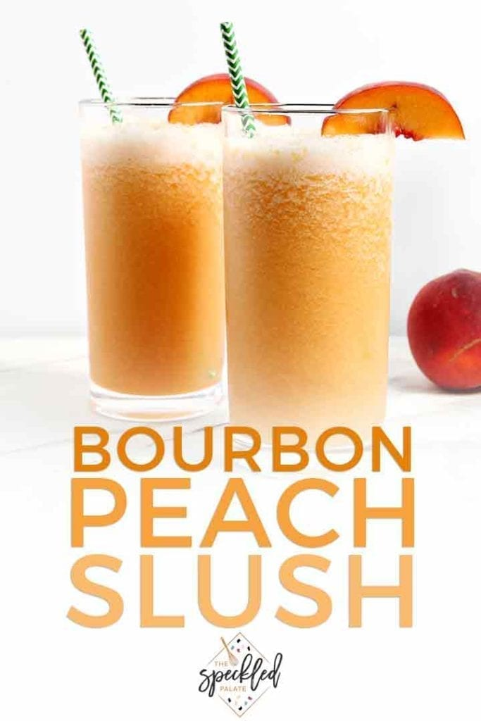"""Two Bourbon Peach Slushes, garnished with peach slices and green chevron straws, sit on a marble tile with text """"Bourbon Peach Slush"""""""