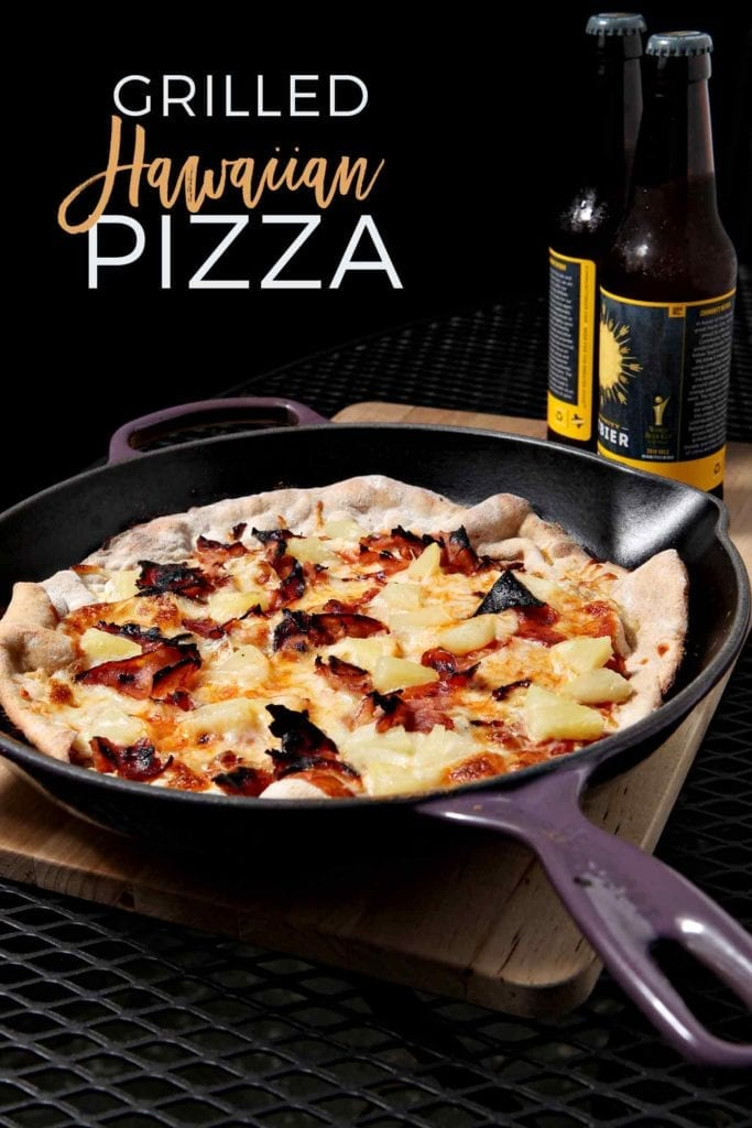 Grilled Hawaiian Pizza, cooked in a cast iron skillet, sits on an outdoor table with beers in the background before eating