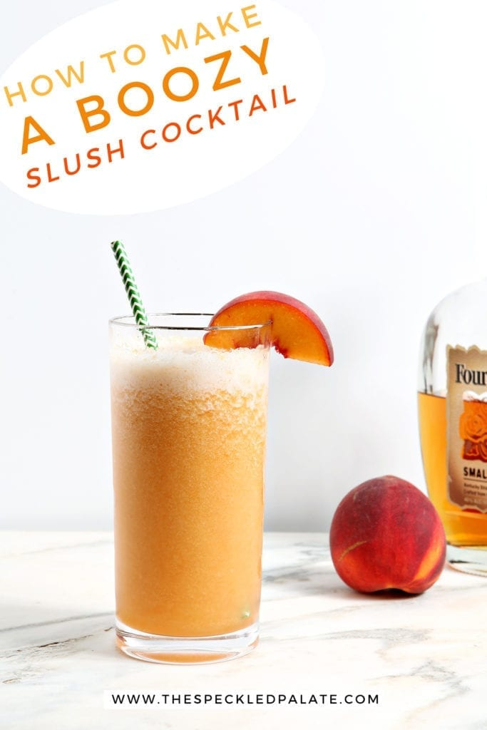 """A single glass holds orange liquid with a green straw and a peach wedge garnish on a marble countertop with a peach and a bottle of bourbon with the text """"how to make a boozy slush cocktail"""""""