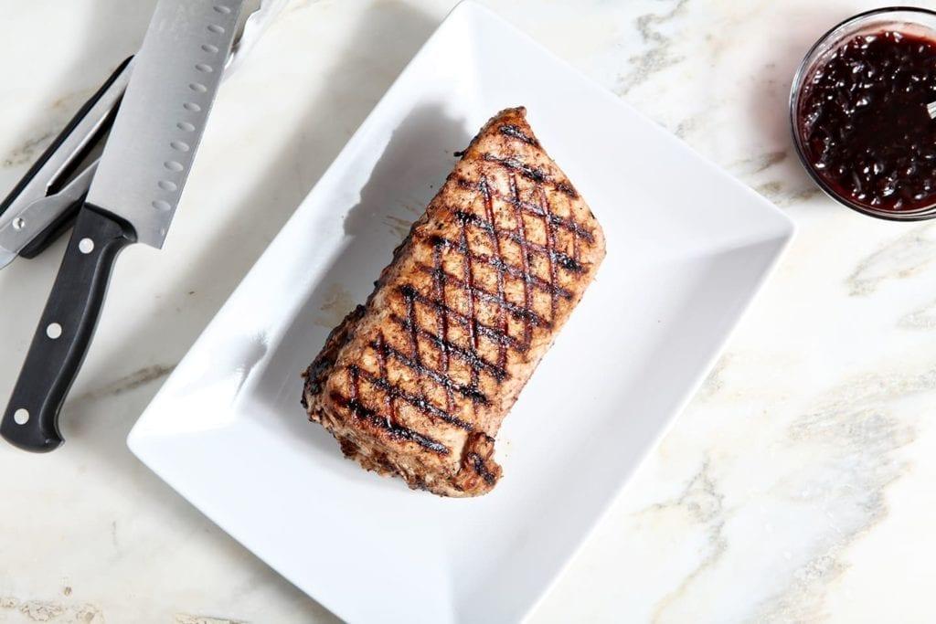Slab of grilled pork tenderloin on white serving platter