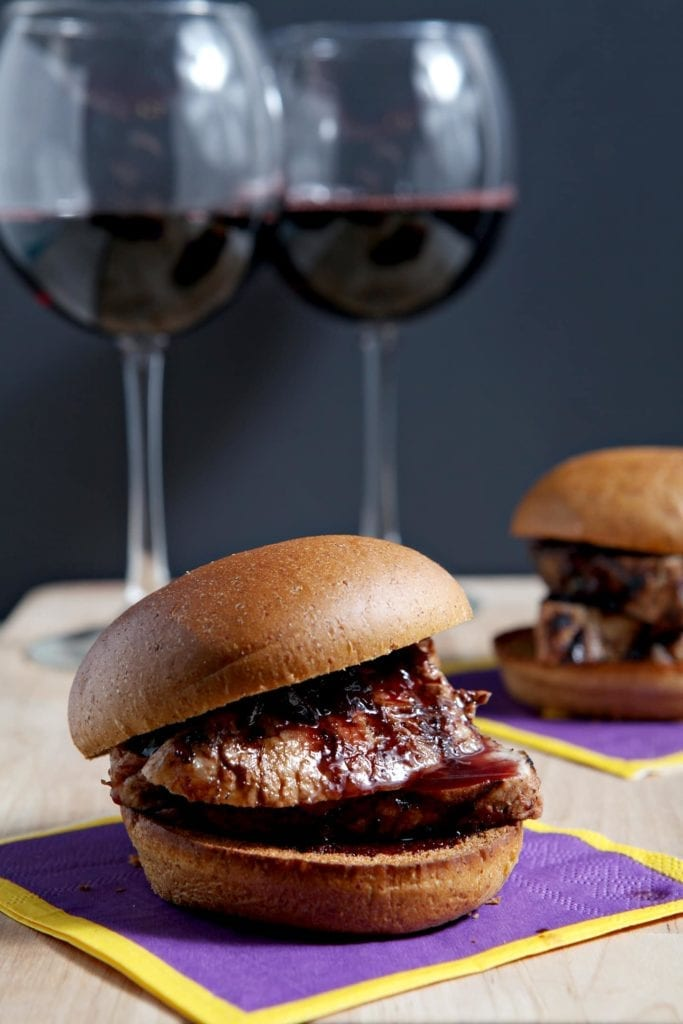Two Pork Tenderloin Sliders with a Red Wine Reduction Sauce are served with glasses of red wine on a wooden board