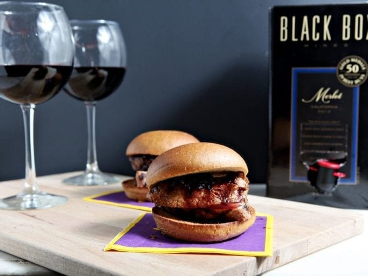 Two sliders in front of two glasses of wine and wine box