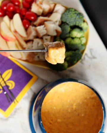 Overhead view of food dipped in bowl of fondue next to party food platter