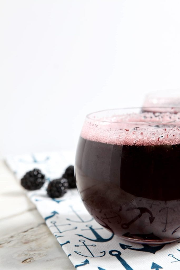 Close up of a blackberry cocktail red wine spritzer on marble