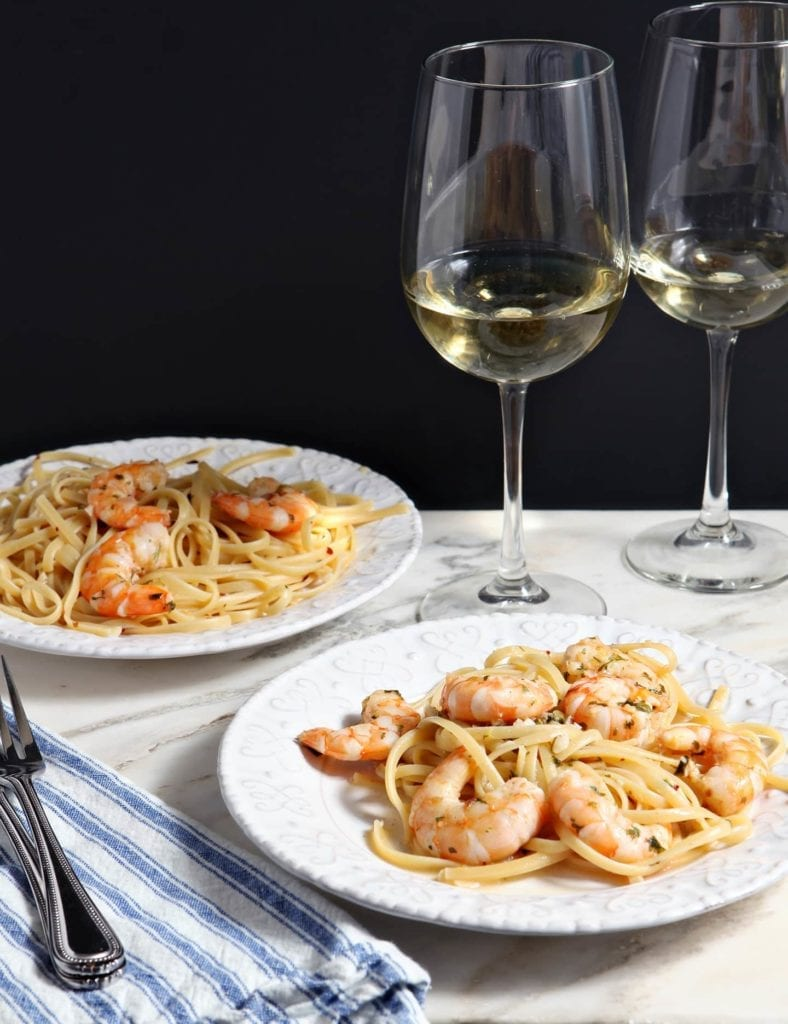 Two white plates hold Lemon Shrimp Pasta on marble with two forks and two glasses of white wine