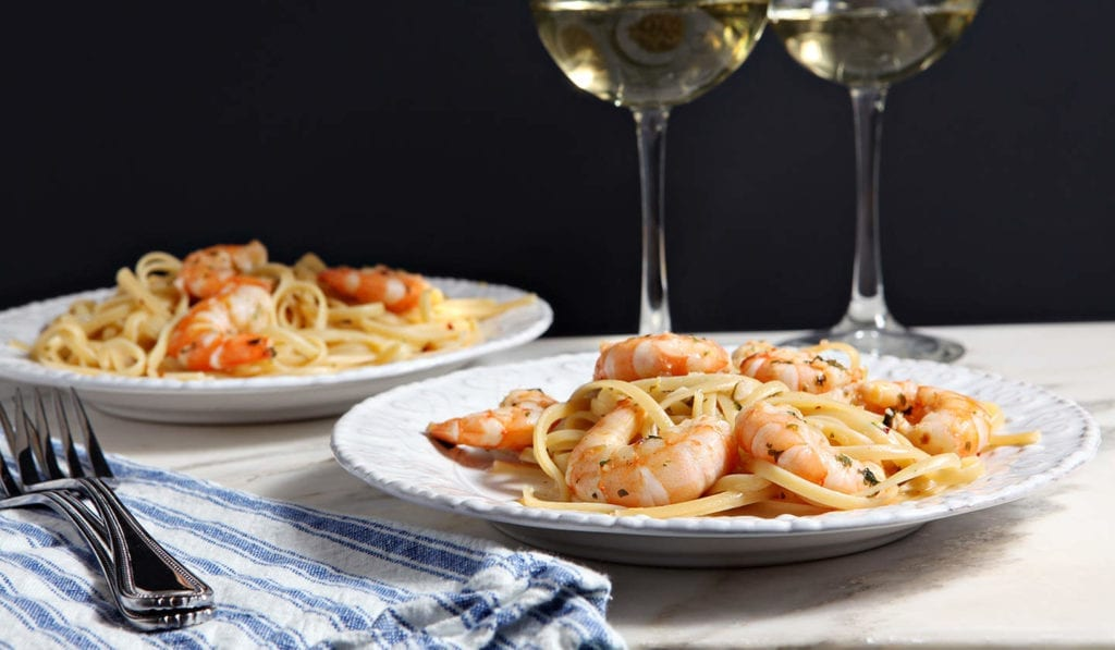 Two white plates of Shrimp Piccata on marble with a blue and white striped towel and two glasses of wine