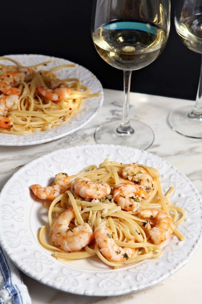 Two plates of Lemon Shrimp Pasta are served with white wine