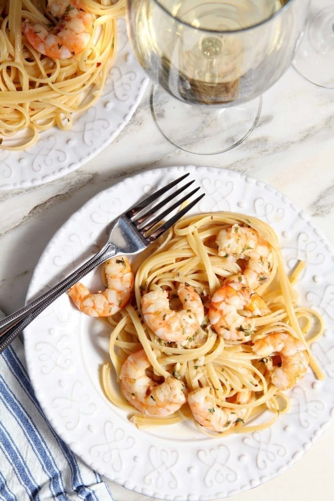 Lemon Shrimp Pasta on a white plate with a fork on marble with a glass of wine