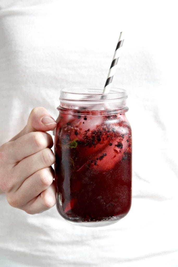 One Blackberry Mint Spritzer being held in hand before drinking