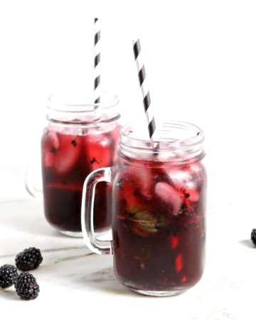 Two Blackberry Mint Spritzer sitting on a marble counter, iced and ready for drinking