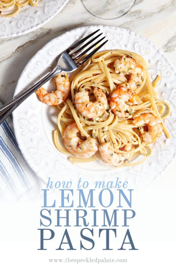 Lemon Shrimp Pasta on a white plate with a fork on marble with a glass of wine with the text 'how to make lemon shrimp pasta'