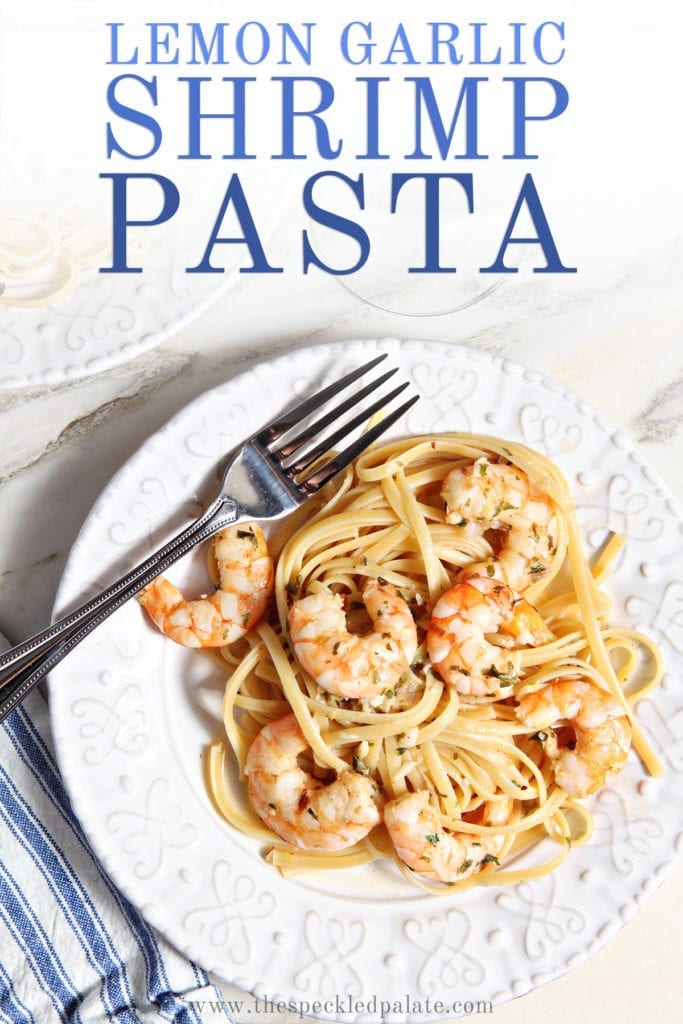 Lemon Shrimp Pasta on a white plate with a fork on marble with a glass of wine with the text 'lemon garlic shrimp pasta'