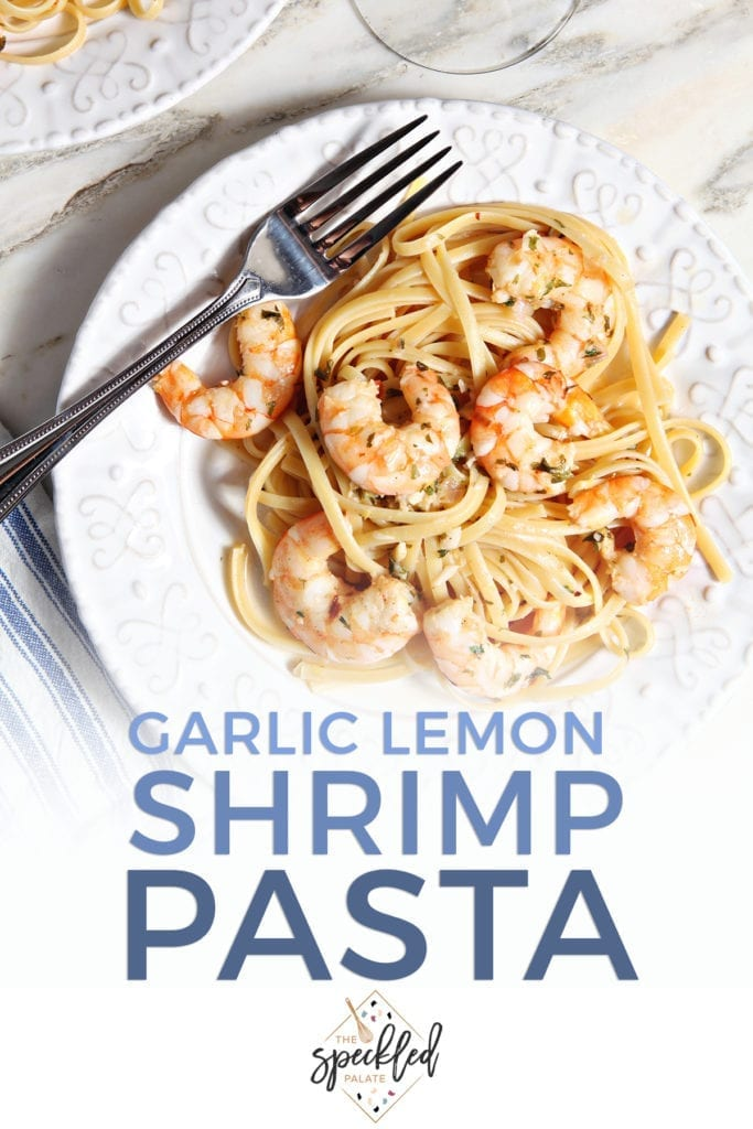 Lemon Shrimp Pasta on a white plate with a fork on marble with a glass of wine with the text 'garlic lemon shrimp pasta'