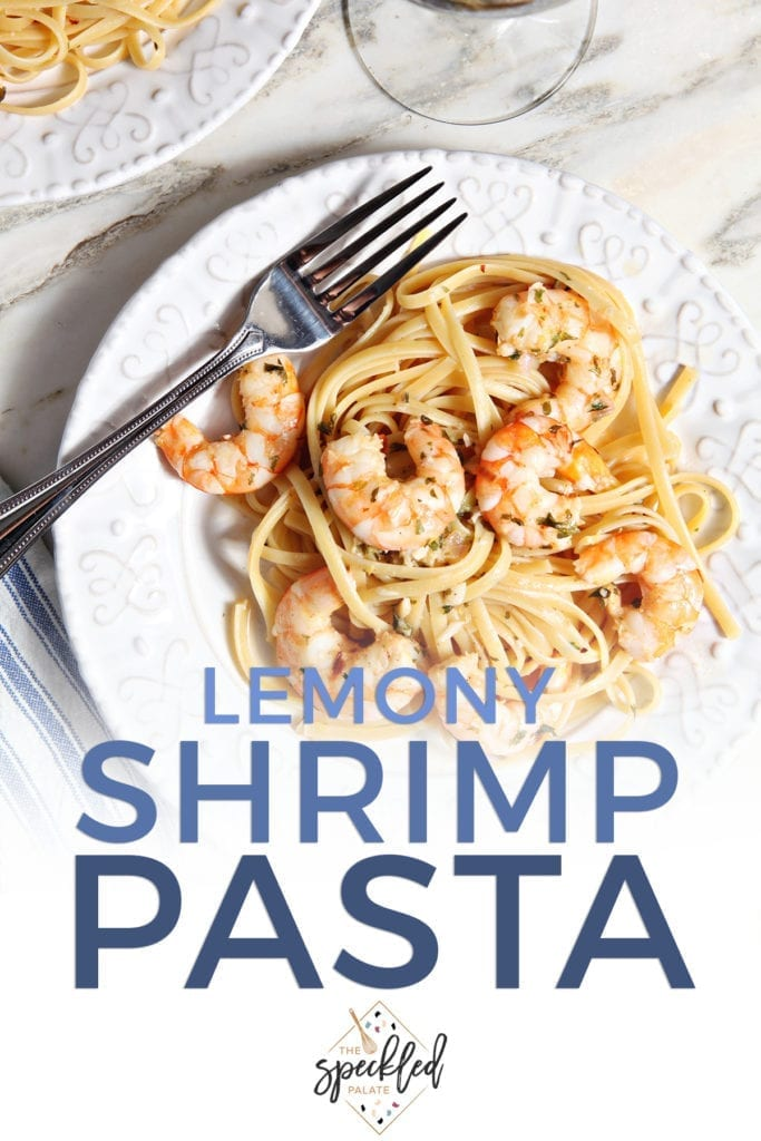 Lemon Shrimp Pasta on a white plate with a fork on marble with a glass of wine with the text 'lemony shrimp pasta'