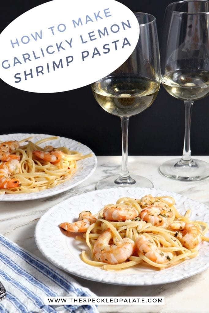 Two white plates hold Lemon Shrimp Pasta on marble with two forks and two glasses of white wine and the text 'how to make garlicy lemon shrimp pasta.'