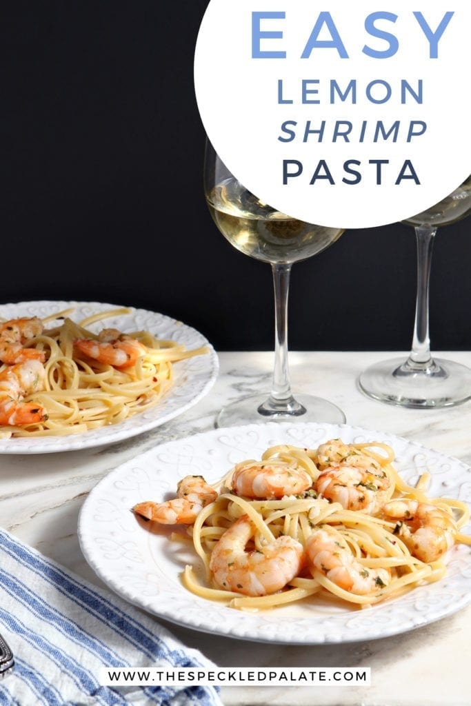 Two white plates hold Lemon Shrimp Pasta on marble with two forks and two glasses of white wine and the text 'easy lemon shrimp pasta'