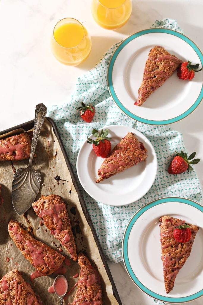 Three plates hold strawberry scones next to a baking sheet with more scones on it