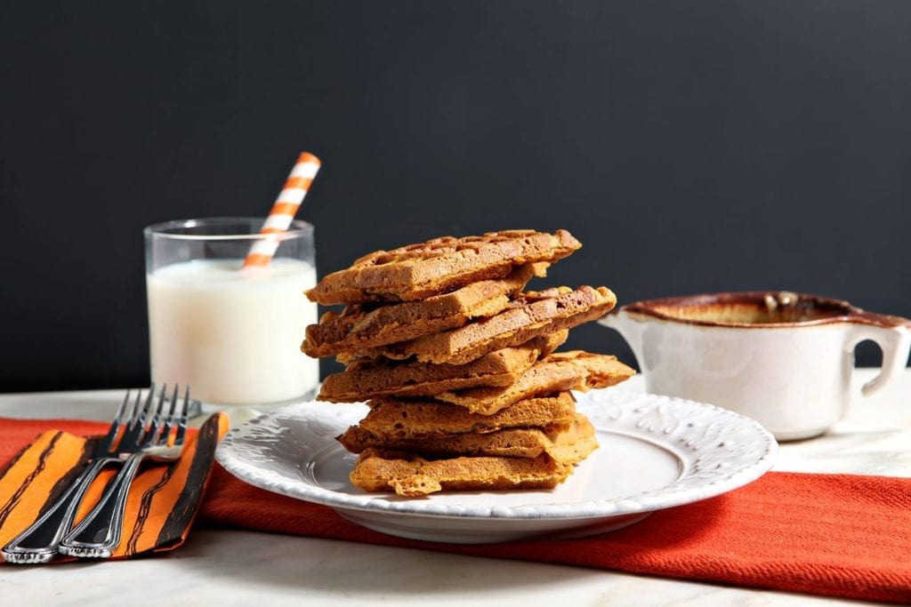A stack of sliced pumpkin waffles on white plate with a glass of milk