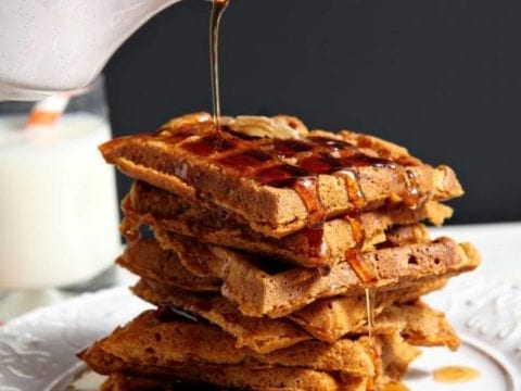 Cinnamon Maple Syrup is drizzled atop a stack of sliced Pumpkin Waffles