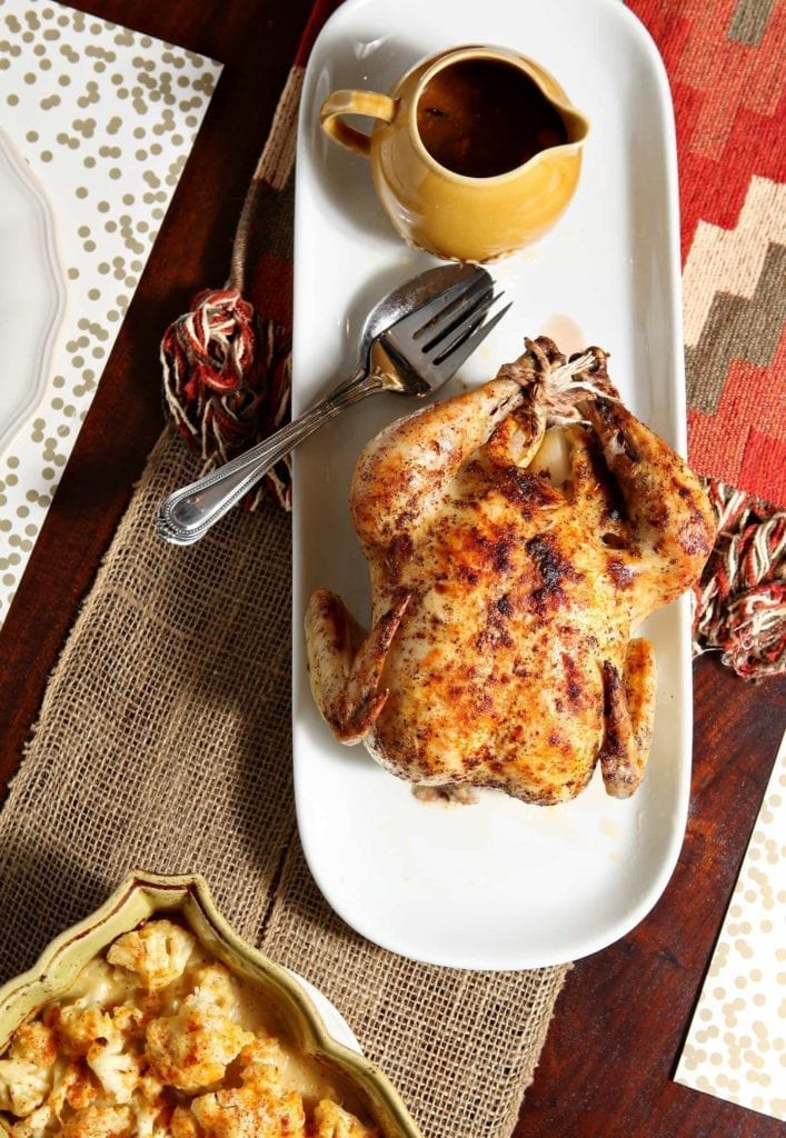 White platter of whole roasted chicken on linens