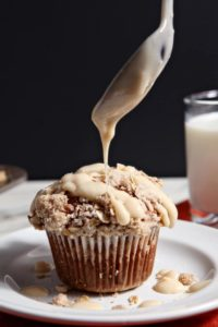 Maple Cream Cheese Glaze is drizzled onto Pumpkin Brown Butter Streusel Muffins.