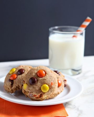 Several Reese's Pieces Peanut Butter Cookies sit on a white plate with a glass of milk