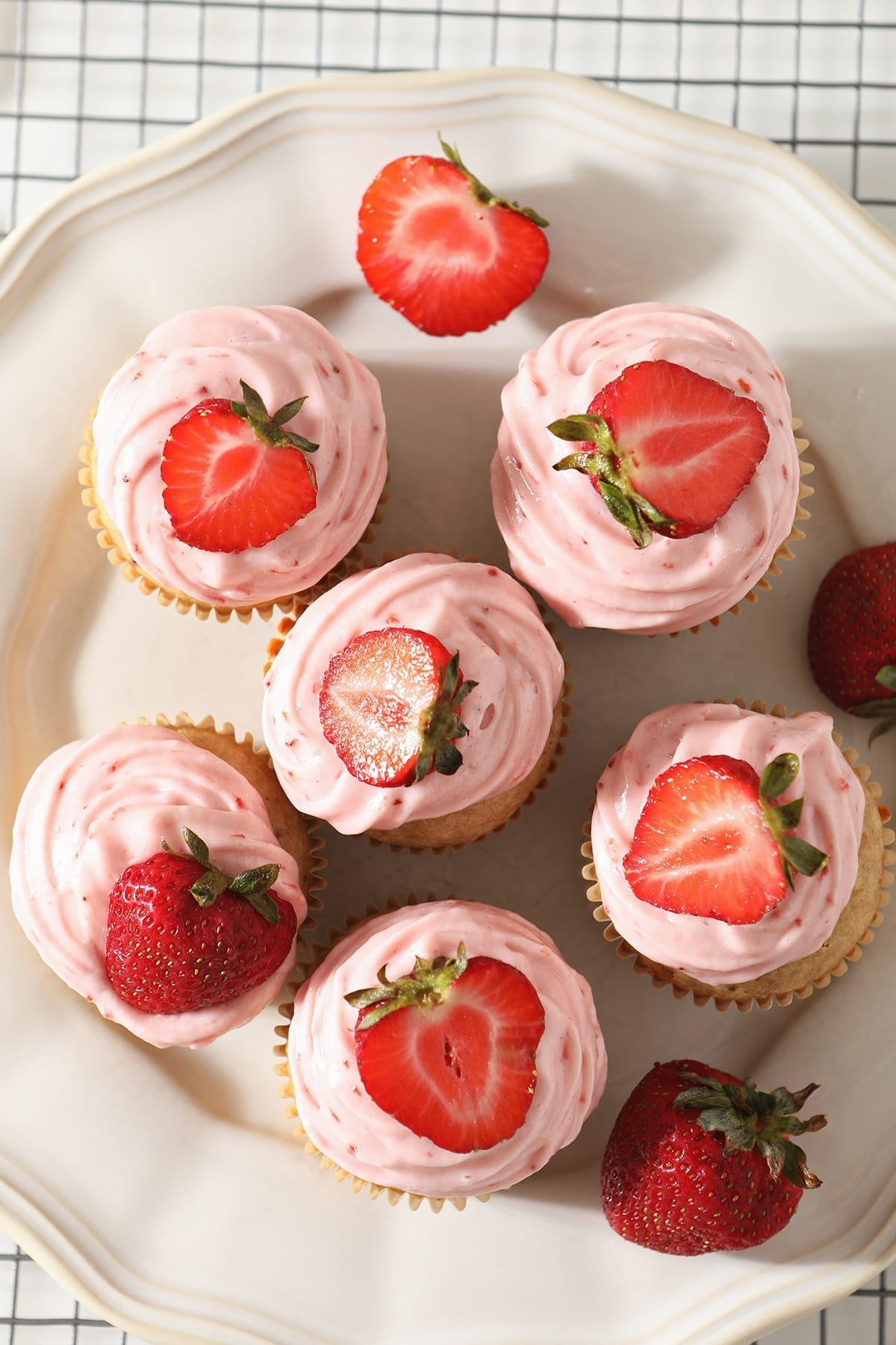 Overhead of a white platter holding six decorated Strawberry Cupcakes