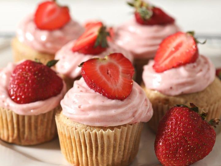 A white platter of decorated Strawberry Cupcakes