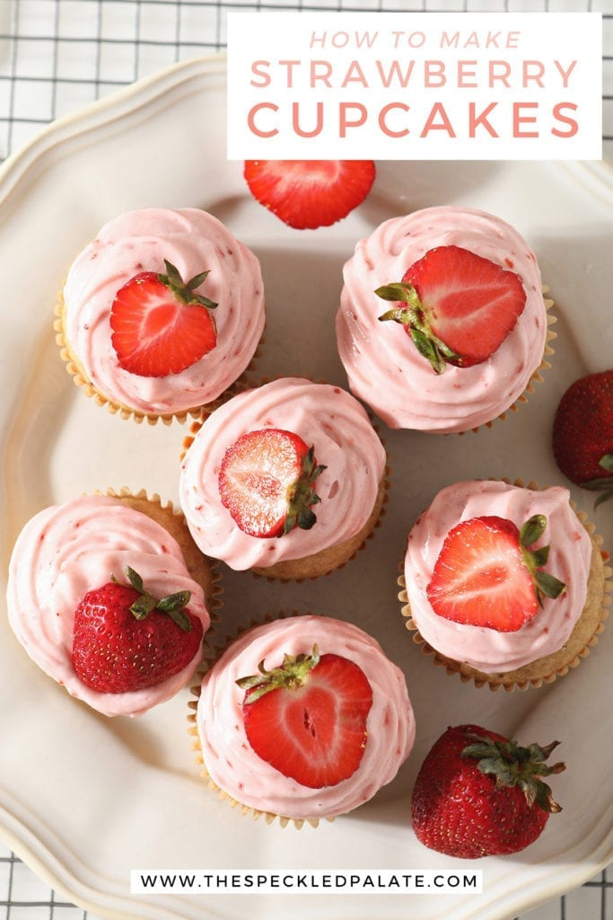 Overhead of a white platter holding six decorated Strawberry Cupcakes with the text 'how to make strawberry cupcakes'