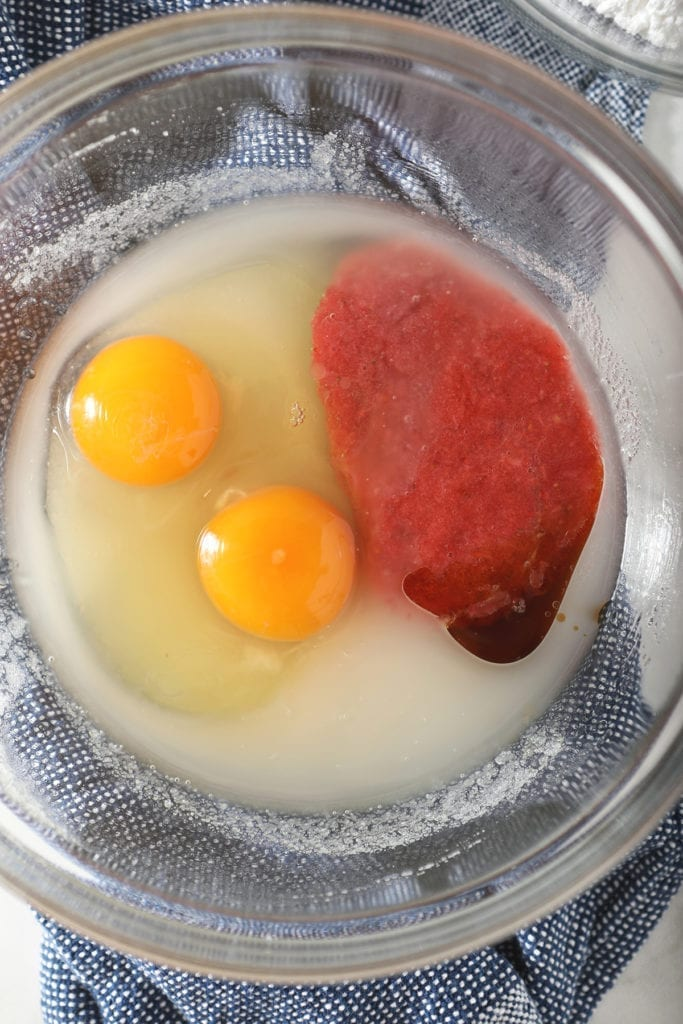 Fresh strawberry puree, eggs, sugar, oil and other wet ingredients in a glass bowl