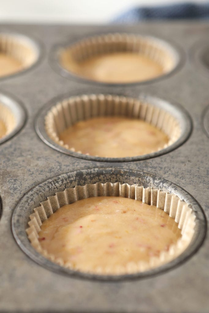 Strawberry cupcake batter in a muffin tin before baking