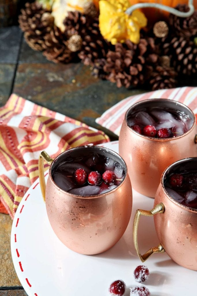 Three Cranberry Mules are served on a white platter