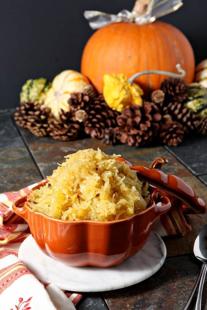 Orange bowl of spaghetti squash on linens in front of autumn décor