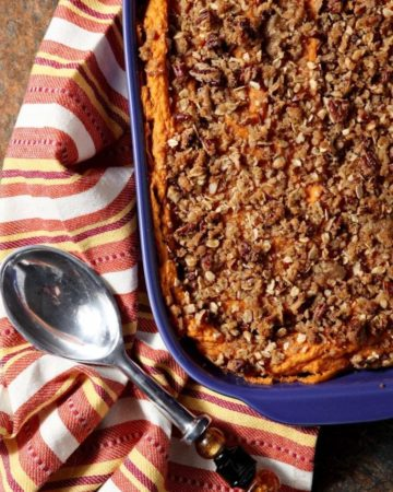 A purple casserole dish holds a Bourbon Sweet Potato Casserole, displayed with an orange towel for serving