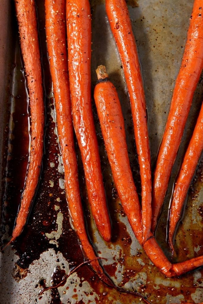 Overhead close up of honey roasted carrots on baking pan