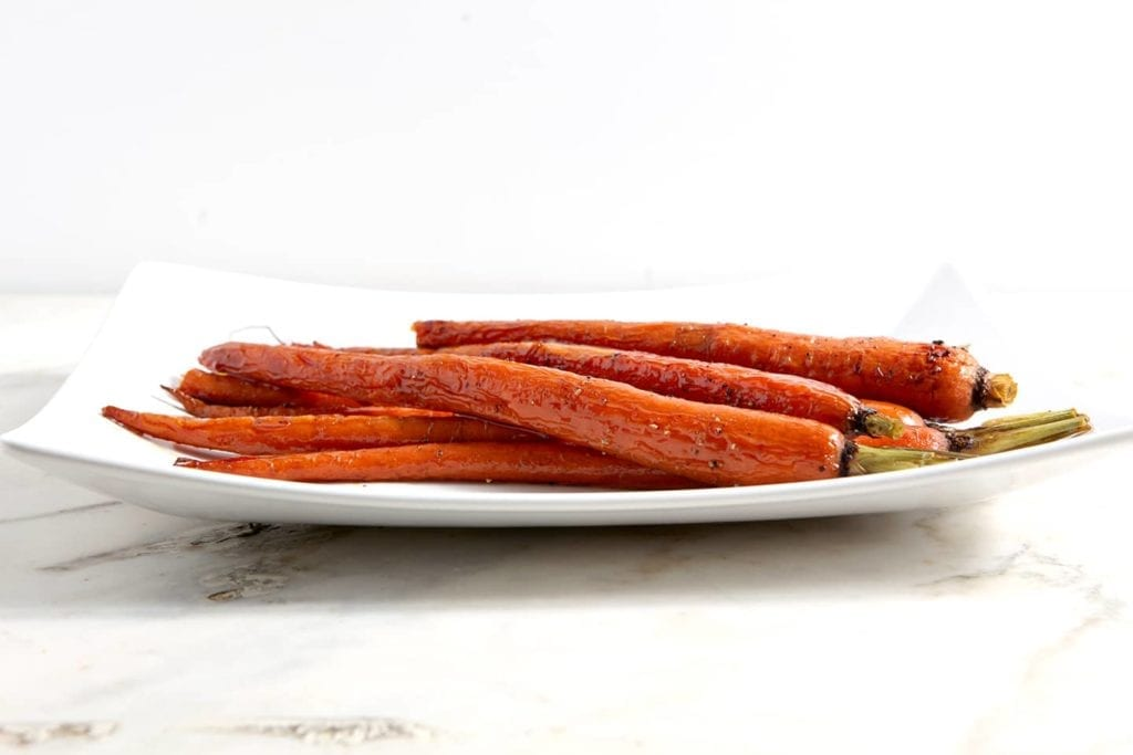 Honey Roasted Whole Carrots laying on a white platter