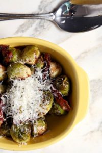 Italian Brussels Sprouts make for a decadent weeknight or Thanksgiving side dish. Brussels sprouts are roasted with prosciutto, then topped with Parmesan cheese once out of the oven. #sidedish #brusselssprouts #parmesan