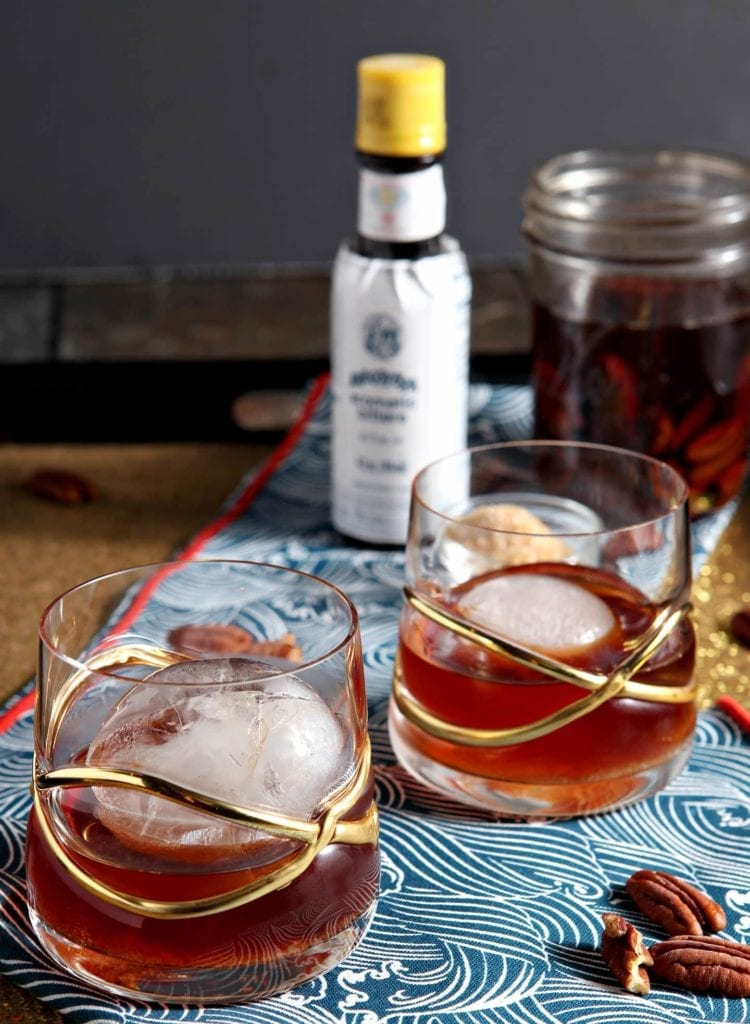A seasonal twist on the classic whiskey cocktail, the Toasted Pecan Old Fashioned is a perfect cocktail for a chilly winter night. Toasted pecans soak in whiskey for days before the infused alcohol is poured atop a sugar and bitter mixture to make an Old Fashioned. #cocktail #whiskey #bourbon #infusedalcohol