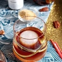 A Toasted Pecan Old Fashioned sits in a fancy glass on a blue and gold background with the ingredients